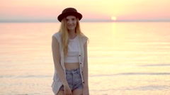 Young blonde girl in hat enjoying summer holidays on the ocean golden sunset Stock Footage