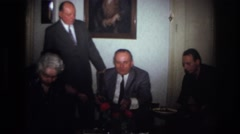 1967: men sitting wearing coat tie talking portrait on walls  Stock Footage