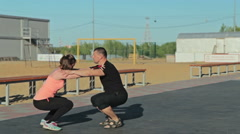 Man and girl squatting together Stock Footage