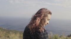 Woman with pink hair standing on the mountain top over blue sea view Stock Footage