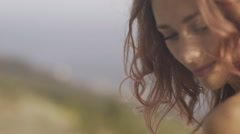 Sexy young woman with pink curly hair sitting on the parapet and posing Stock Footage