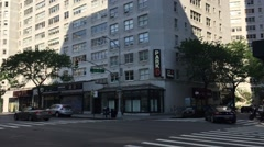 Establishing shot DX pan up to windows of apartment building oin eastern Midtown Stock Footage