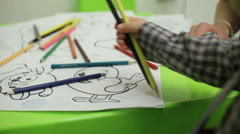 Coloring book and pencils in hands of children Stock Footage