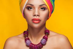 Afro american girl in national turban over yellow background Stock Photos