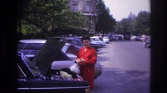 1967: a young beautiful lady in red dress standing near to the car parked PARIS Stock Footage