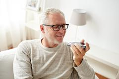 Old man using voice command recorder on smartphone Stock Photos