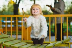 Close up portrait of cute girl playing xylophone outdoor Stock Photos