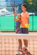 Instructor or coach teaching child how to play tennis on a court indoor Stock Photos