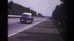 1967: vehicles are streaming on the highway flanked by trees PARIS FRANCE Stock Footage