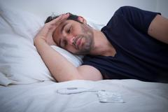 Depressed man lying in his bed and feeling bad Stock Photos