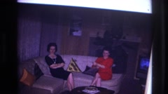 1967: women sitting on couch in living room man standing sitting between ladies Stock Footage