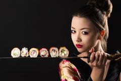 Beautiful girl samurai with sword and rolls Kuvituskuvat