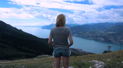 CINEMAGRAPH - Young female looking down on a lake from the top of mountain Stock Footage