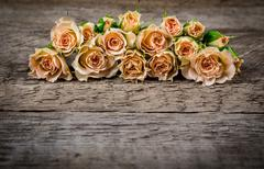 Bouquet of little beige roses on wooden rogue table Stock Photos