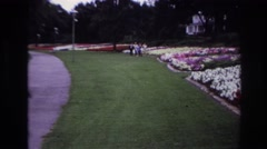 1967: people, probably famous people walking on grass besides flowers and waving Stock Footage