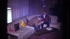 1967: two older men sitting on a couch are joined by a woman in a red dress. Stock Footage