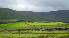Green pasture and a mountain in Carrowmore Ireland Stock Footage