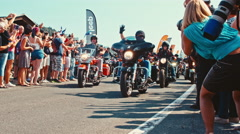 Bikers wave to the spectators right at the beginning of the motorcycle parade Stock Footage