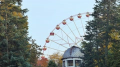Ferris wheel rotates in a park in the foreground roof observatory Stock Footage