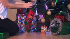 A woman decorates a beautiful christmas tree in a house.  Stock Footage