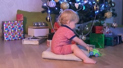 Christmas concept. Little baby boy playing with toy car near the Christmas tree Stock Footage