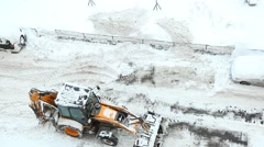 Backhoe loader scrape snow by claw bucket plow, high angle shot with sound Stock Footage