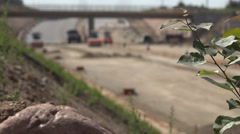 Highway road construction site machinery and workers and blurred tree branch Stock Footage