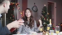 Caucaion man gives beautiful Japanese women christmas present at party Stock Footage