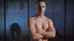 Handsome muscular man with arms crossed posing shirtless at the gym Stock Footage