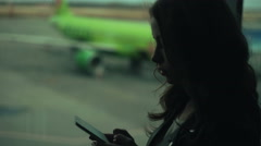 Female typing sms on smart phone near the airport window. Stock Footage