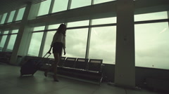 Woman in heels goes at airport and roll suitcase on wheels. Stock Footage