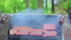 Fotage of a person putting cevapcici on a grill Stock Footage
