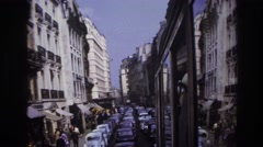 1967: view of a european city street packed with traffic and people walking on Stock Footage