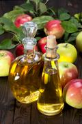 Apple cider vinegar in a glass vessel and apples Stock Photos