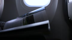 Girl looks magazine in an airplane Stock Footage