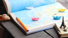 Travel to World idea or Holiday. Paper boats on the map and the Eiffel Tower Stock Footage