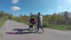 Young stylish mother walking with her baby in city Stock Footage