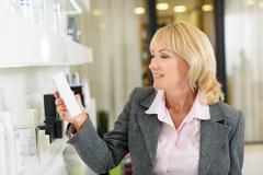 Mature lady buying cosmetics in store Stock Photos