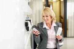 Middle-aged lady buying cosmetics in shop Stock Photos