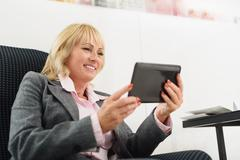 Cheerful businesswoman using gadget during anticipation Stock Photos