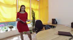 Working day. Pretty young brown-haired woman dancing at the desk in a office. 4K Stock Footage