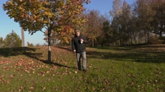 Man with cane drink coffee and walking in the park Stock Footage