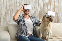 Dog and bachelor wearing virtual reality glasses Stock Photos