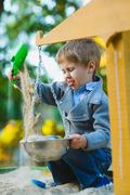 Happy little boy playing in sandbox at playground Stock Photos