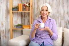 Happy old lady drinking hot beverage at home Stock Photos