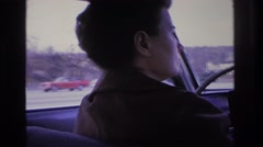 1966: woman driving looking back cars passing highway houses trees street lamps Stock Footage