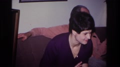 1966: a woman, who appears to be uncomfortable, sitting next to a man on a couch Stock Footage