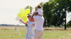 Young family walking on rural footpath and holding hands them baby on sunset Stock Footage