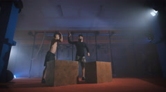 Two men doing a box jump at the gym Stock Footage