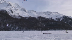 Snowkiters on a frozen lake in the Switzerland Alps Stock Footage